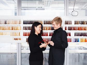 Two employees are discussing in the test salon.