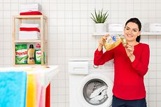 Woman dispensing Silan in front of washing machine.